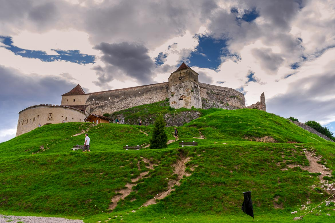 This is an image of Rasnov Fortress. The fortress is built on a green hill and is surrounded by defensive walls.