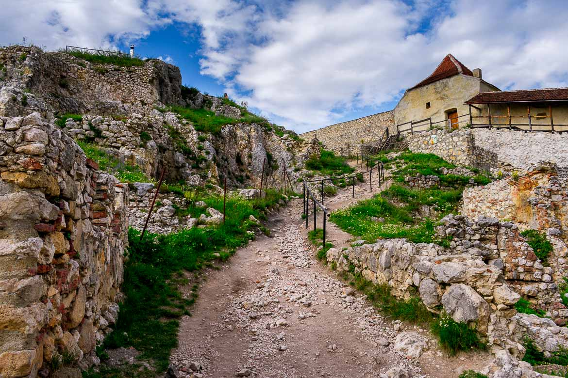 This image shows the interior of Rasnov Fortress. There are narrow dirt streets that wind their way around the fortress.