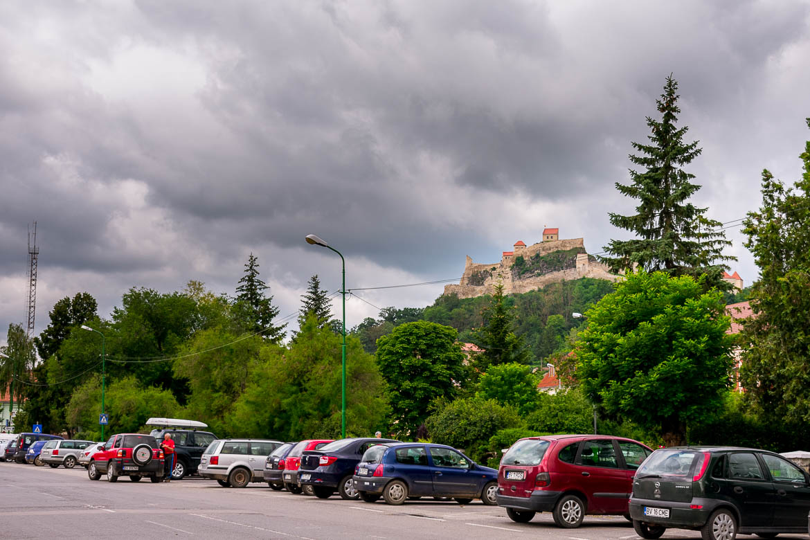 This image shows a line of cars parked at a designated area in Rupea town. In the background, we can see Rupea Fortress perched on a hill overlooking the town.