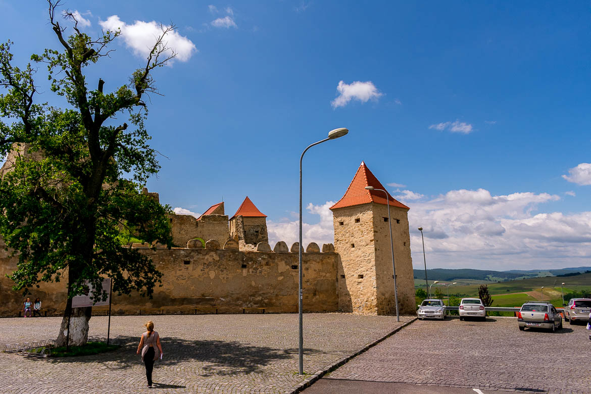 This is an image of the free parking lot right outside Rupea Fortress. We can see 3 towers of the fortress as well as 4 cars parked. There is also Maria on her way to the fortress on the far left side of the photo.