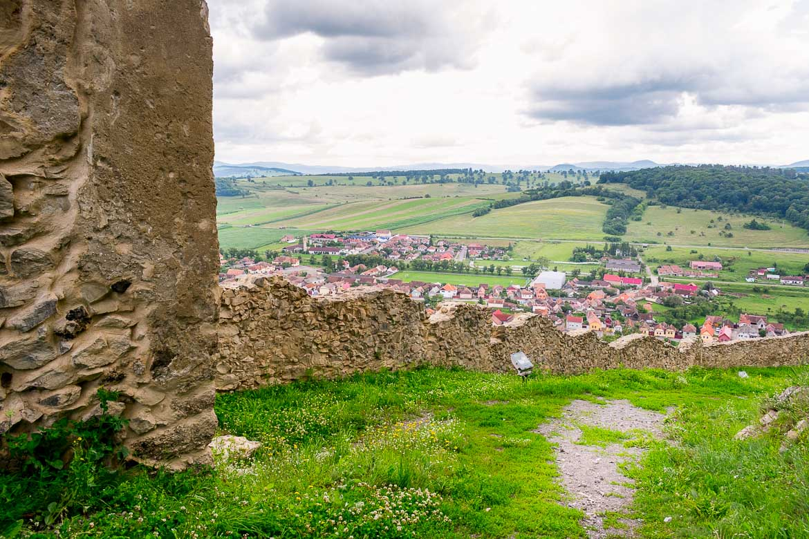 This image was shot inside Rupea Fortress. It shows part of the fortifications in the foreground. In the background, there is a fantastic view to Rupea town below and the green rolling hills in the distance.