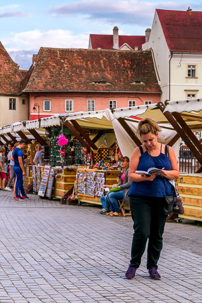 This is an image of Maria standing in the middle of Piata Mica (Small Square) going through the pages of our Lonely Planet guidebook. Behind her, there are stalls selling souvenirs.