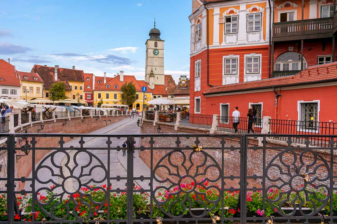 This is an image of Sibiu Old Town. In the foreground, the iron cast Bridge of Lies, one of the city's most popular attractions. In the background, the Council Tower dominated the blue sky.