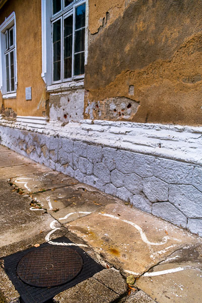 This image shows the exact spot where Nicolae and Elena Ceausescu were executed on Christmas day 1989. There are many bullet holes on the wall. There are also the silhouettes of the dead bodies painted on the ground.