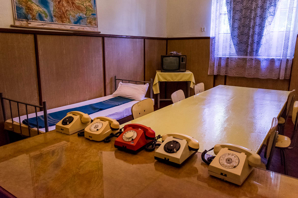 This image shows the interior of one of the rooms at the military barracks in Targoviste. There is a single bed, a table with an old-fashioned TV, a table with 6 chairs and another table with 5 retro telephones on it.