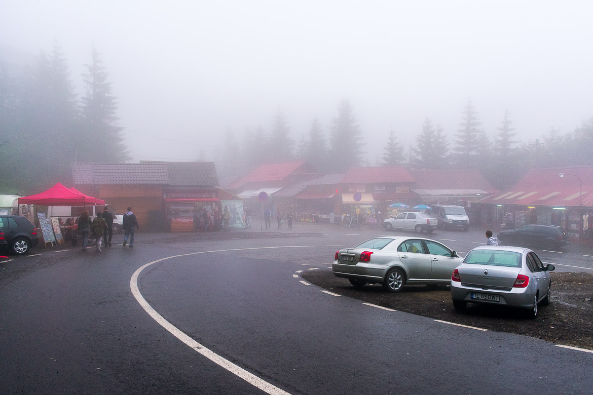 This is an image of the parking area near Balea Waterfall. There are many shops selling souvenirs and snacks in the background. Everything is almost completely covered in fog.