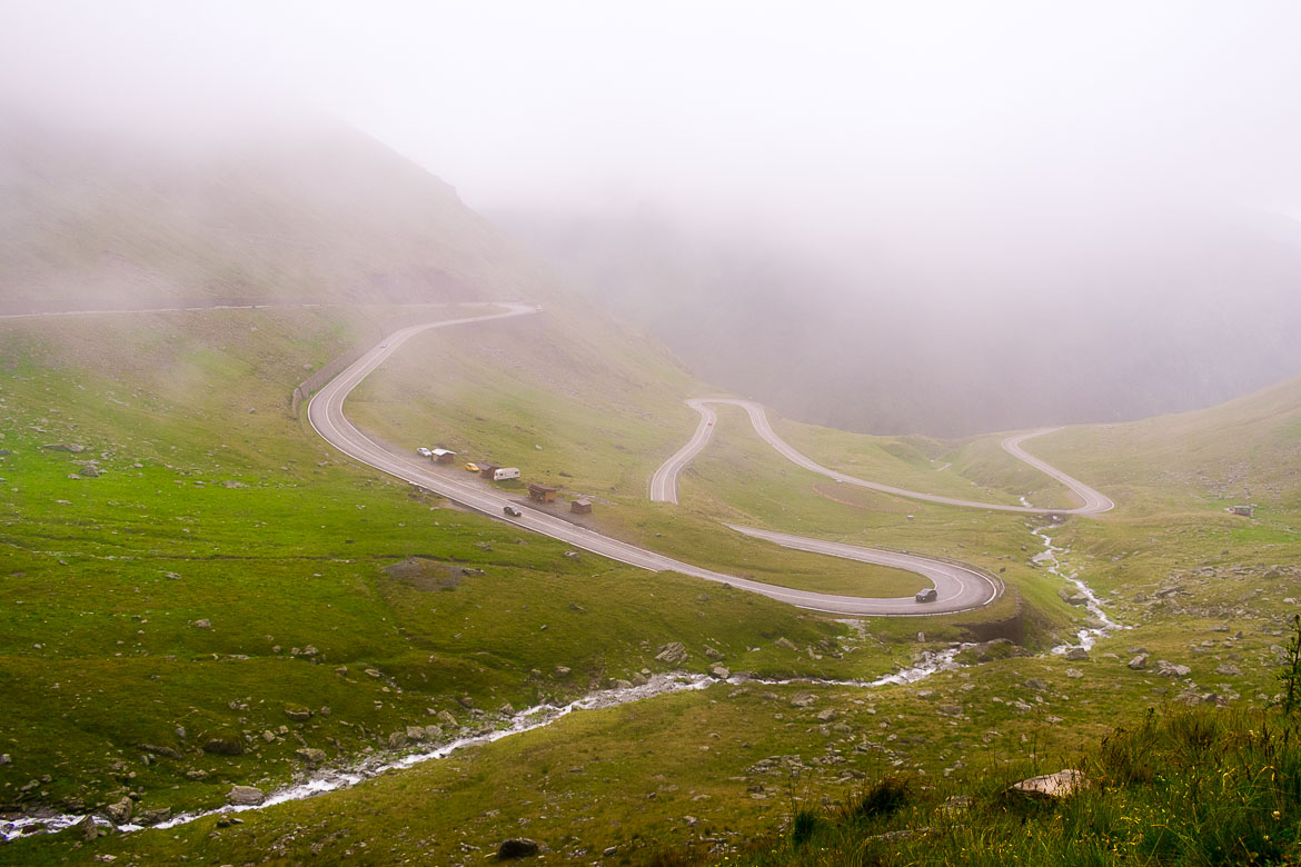 This image shows the Transfagarasan hairpin turns. The Transfagarasan Road winds its way through lush greenery and running streams. It was definitely the highlight of our entire Romania road trip.