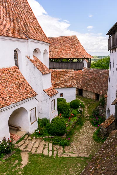 This image shows the interior of the fortified church in Viscri. It is a complex of buildings which look like one. The church is surrounded by green plants and pretty flowers. The walls are white and there are red tiled rooftops.