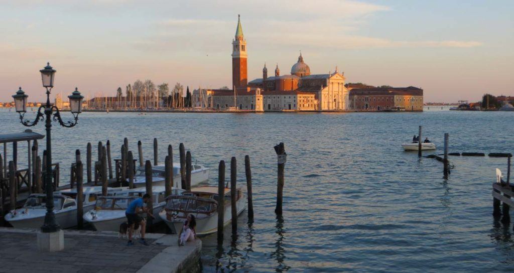 This photo shows the island of San Giorgio Maggiore in Venice, Italy during sunset. What to do in Venice: our complete guide to La Serenissima.