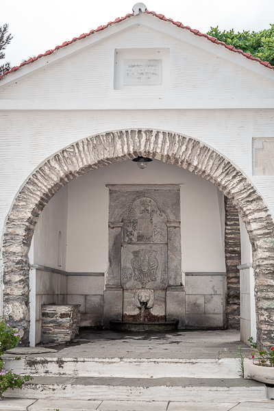 This image shows Sariza Spring in Apikia village. It's an arched, covered building and the water runs from a marble lion's mouth.