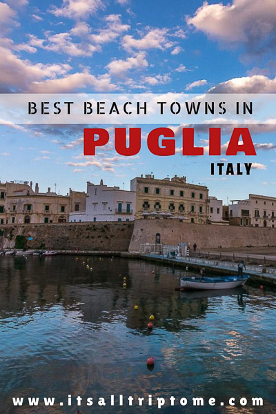 This photo shows Gallipoli in Puglia Italy. It is almost sunset and the clouds have pinkish hues which also reflect on the calm sea. There are a few fishing boats at the small port and a line of old fashioned buildings. This is an optimised image for Pinterest. There is text on it that reads: Best beach towns in Puglia Italy. If you like our article, pin this image.