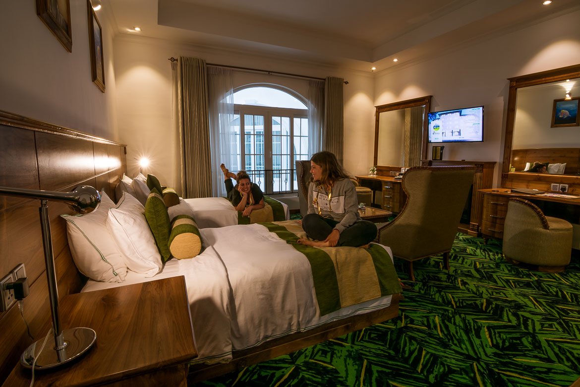 This photo shows the interior of our room at Araliya Green City Luxury hotel. There is a green carpet and classic furniture and each of us is sitting on her bed while we chat.