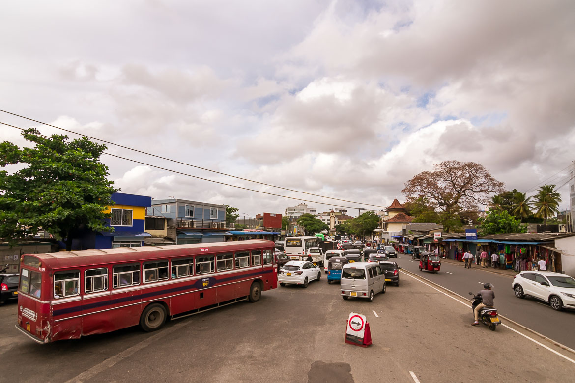 This is a photo of downtown Colombo in Sri Lanka. We can see many cars on a main road with high traffic.