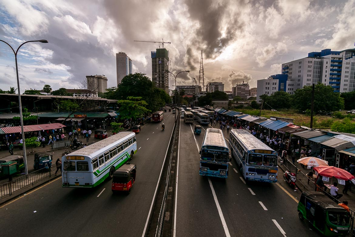 This is a photo of an avenue in Sri Lanka as seen from a bridge. There is a dramatic sky and many colourful local buses on the road. This is the photo we chose to be the featured image on our article: How to spend 2 days in Colombo Sri Lanka.