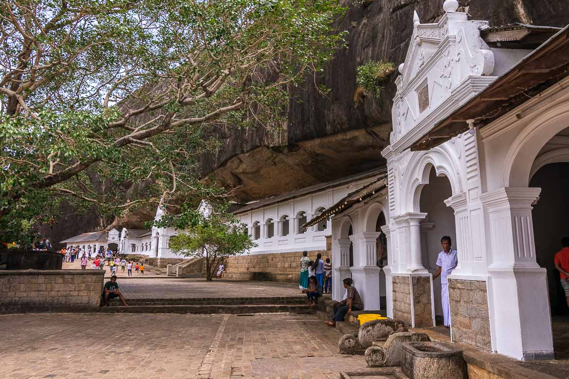 This is a photo of the outside of the Dambulla Cave temple. There are many small buildings built at the foot of the rock as well as a huge tree in front of them. The tree is an essential part of any Buddhist temple.