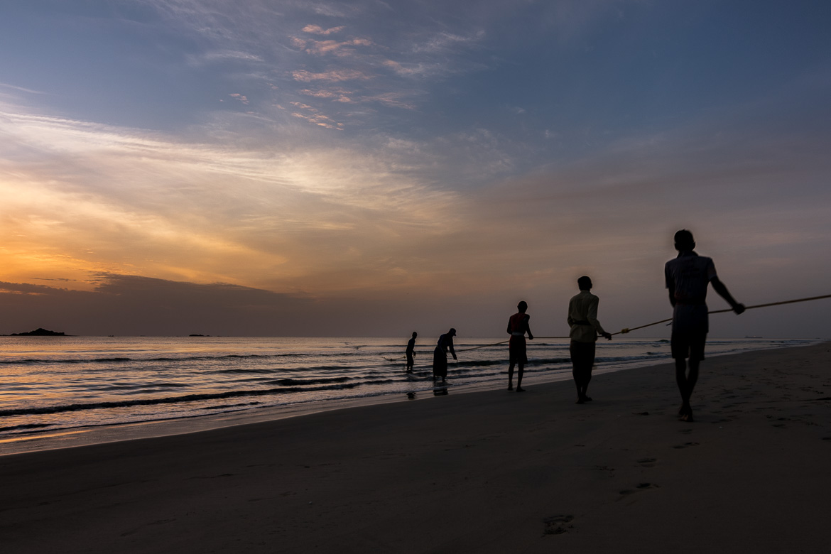 This photo was taken at dawn on Nilaveli Beach. It shows local fishermen pulling out their nets from the sea.