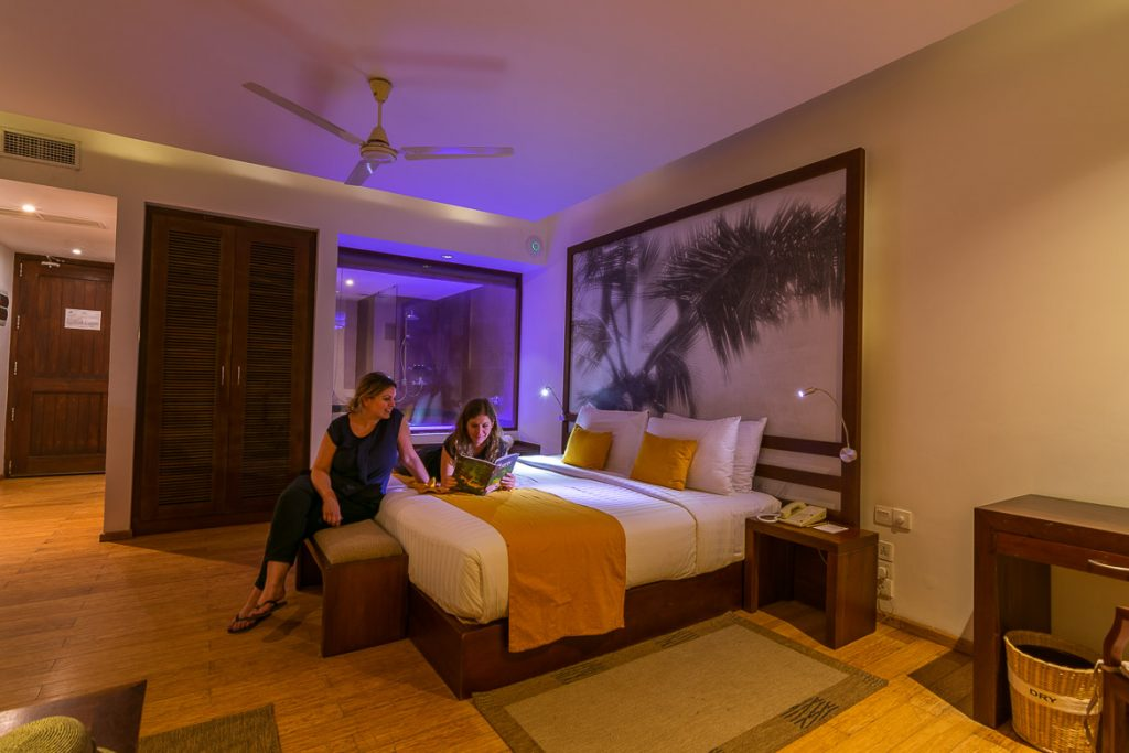 The interior of our room at Jetwing Sea Hotel. We are sitting on the bed reading a book about sri Lanka.