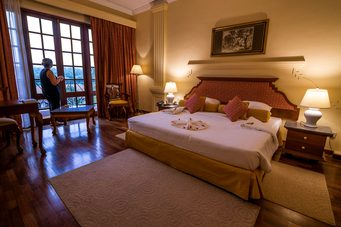 This photo shows the interior of a room at the amazing Mahaweli Reach hotel in Kandy. It is decorated in old-fashioned yet luxurious style. Maria is standing at the window looking out to the garden.