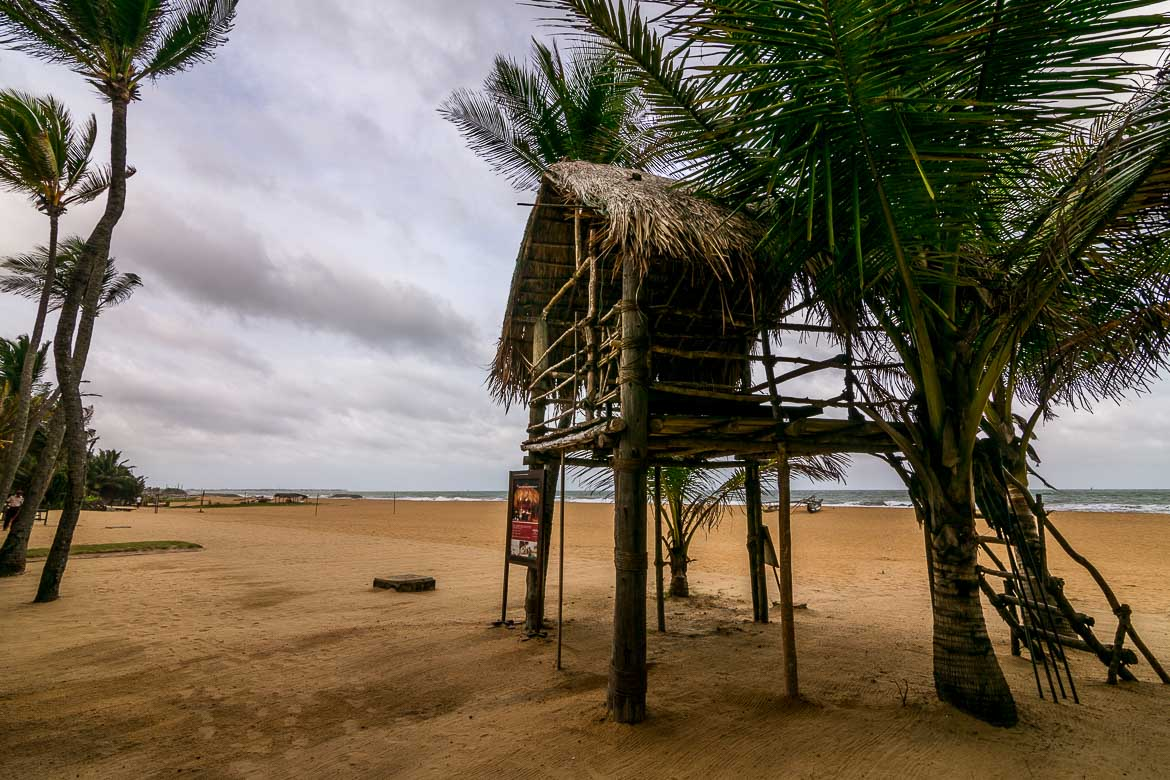 This image shows a tree house on the golden sand of Nilaveli Beach. At the background, huge waves are crashing on the beach. The photo was shot from the balcony of a room at Jetwing Sea Hotel.