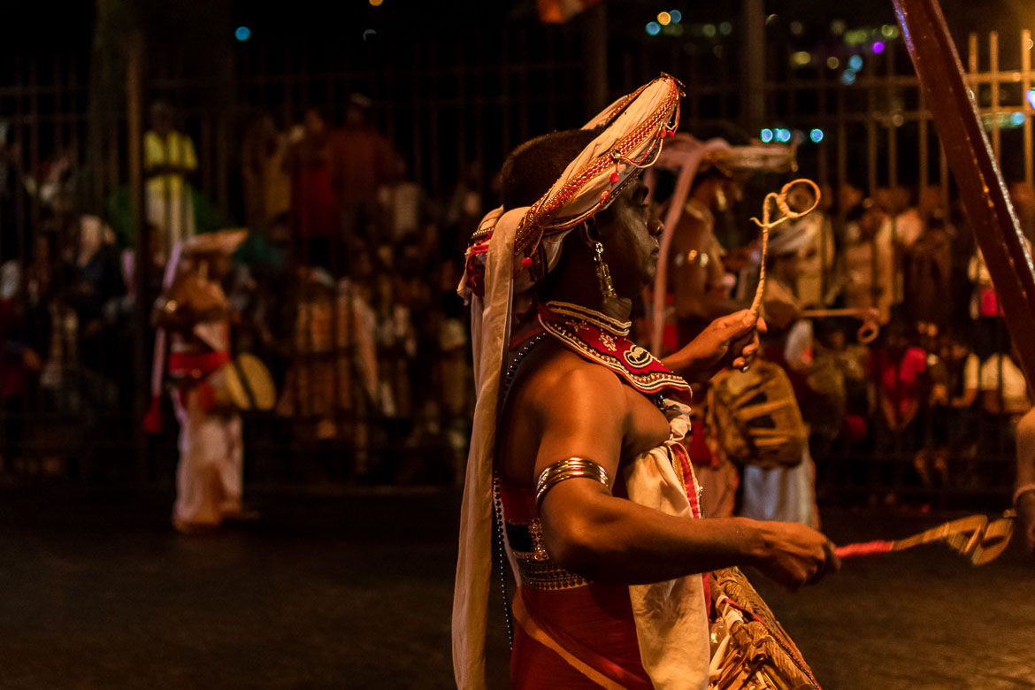 This is a close up of a couple of dancers in their traditional costumes during the Perahera procession.