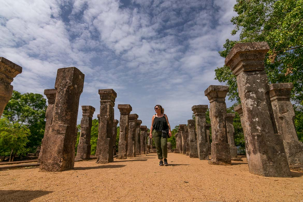 This image shows Maria walking among the ruins of the Council Chamber of King NissanKamalla in Polonnaruwa on a sunny day.