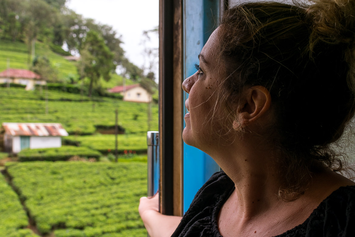 This is a photo of Maria gazing at the glorious tea fields from the open door on board the train to Nuwara Eliya.