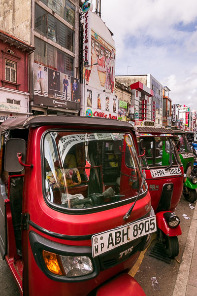 This image shows a line of parked tuk-tuks on a central road in downtown Colombo. Tuk-tuks are painted in bright colours. We can see 2 red and one green tuk-tuk.