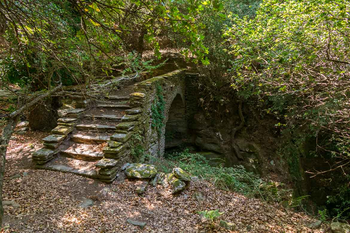 Epaminondas Bridge, an old stone bridge, among lush greenery. 13 unique things to do in Andros Greece and full Andros Guide.