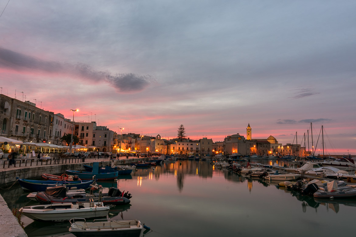 This photo shows Trani at sunset. Everything is dyed in hues of orange and pink: the sea, the sky, the old palazzi.