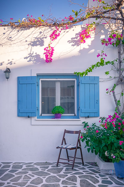 This is a photo of a traditional house in Antiparos Town with sky blue shutters and a fuchsia bougainvillea.