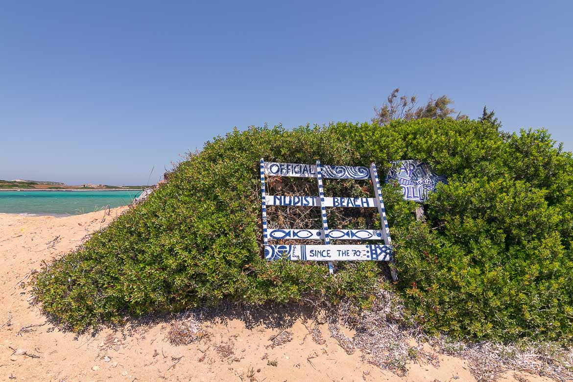 This is a sign at the Camping Beach. It reads Official Nudist Beach since the 70s. It is placed on a bush on the sand and we can see the turquoise sea in the background.
