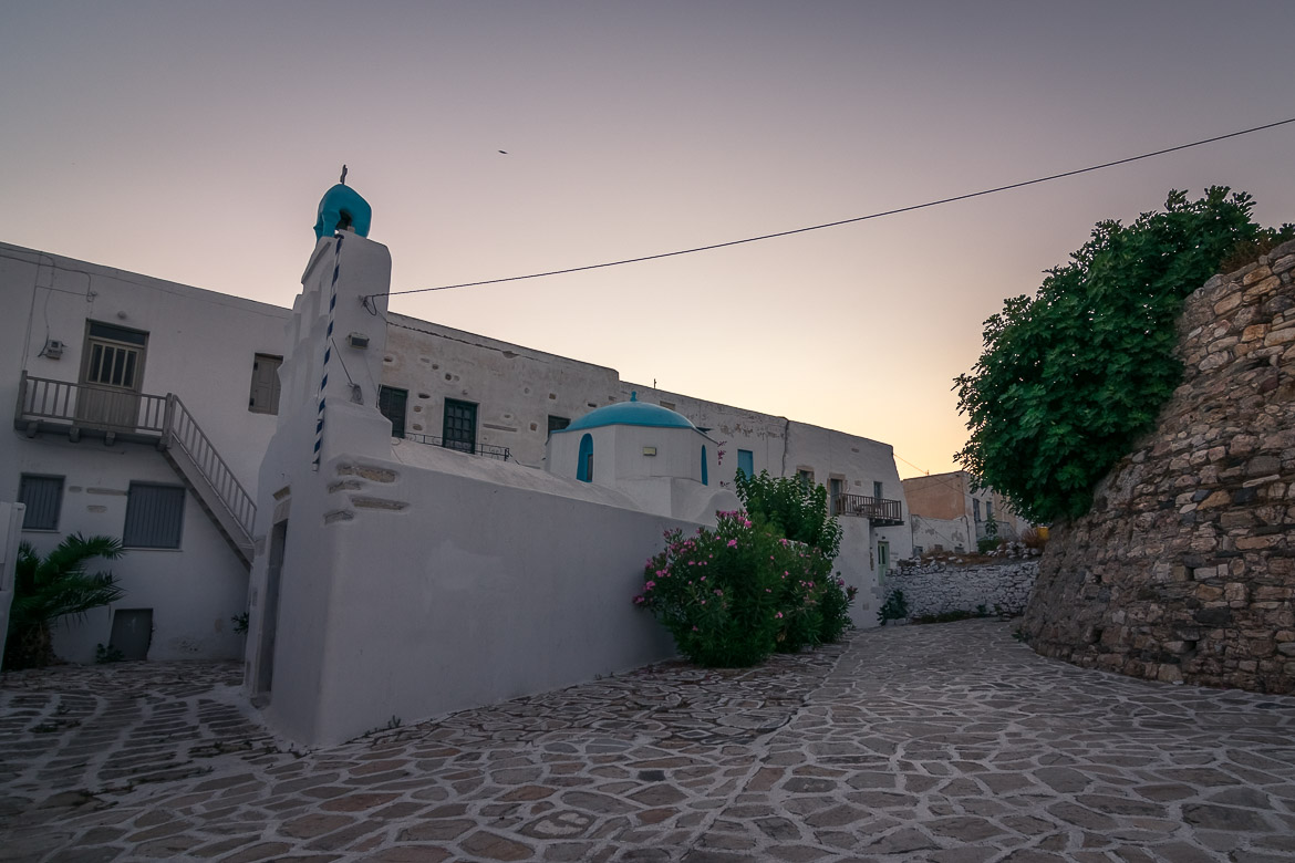 This image shows the castle of Antiparos at sunrise. We can see the remains of the castle tower and a tiny whitewashed church.