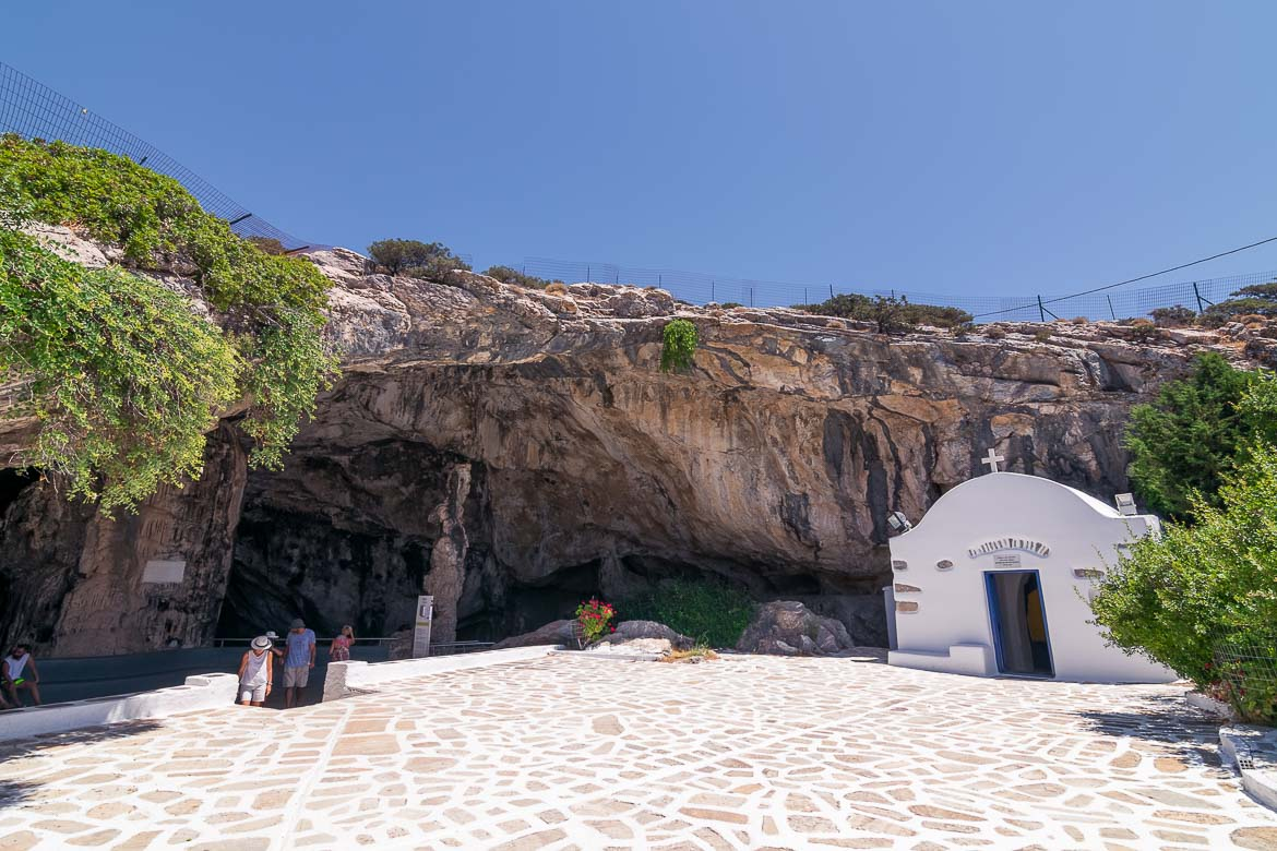 This image shows the entrance to Antiparos Cave. There is a large open space and a small church.