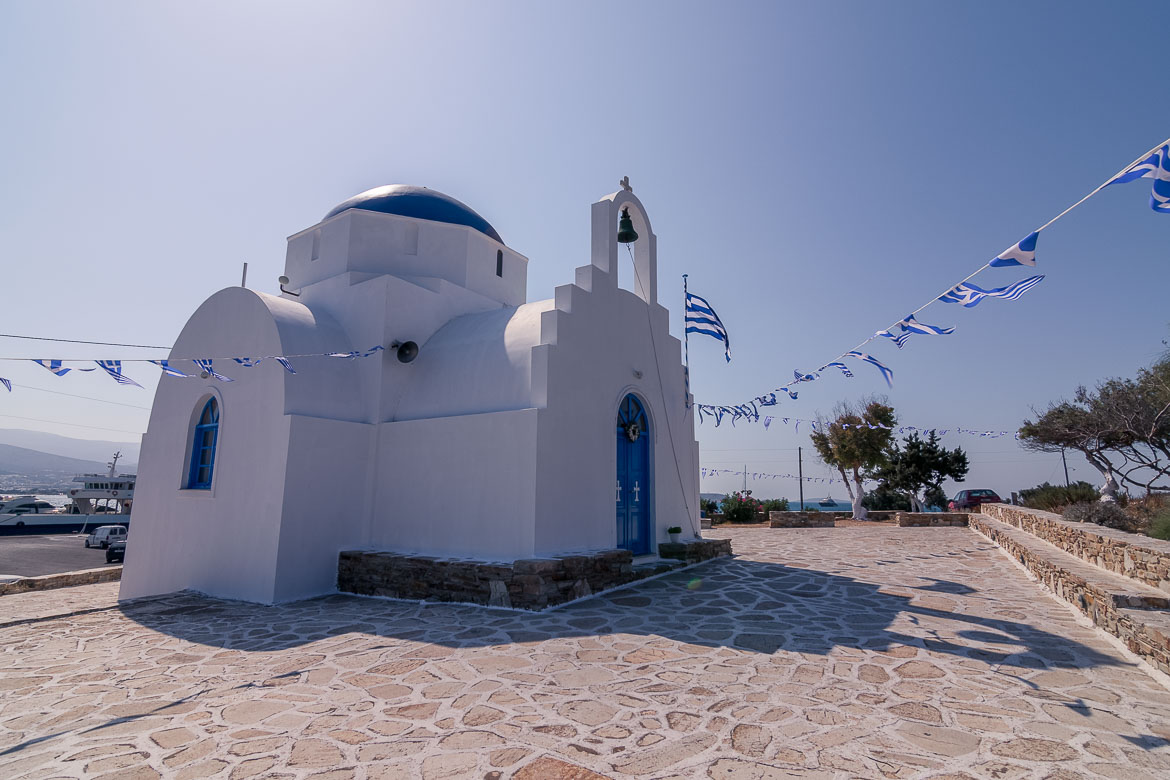 This is a photo of Santa Marina Chapel, a small whitewashed church with a blue dome near the port of Antiparos.