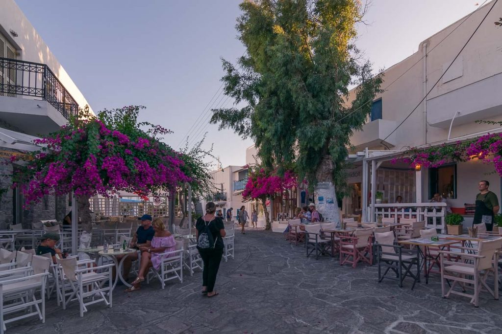 This is a photo of Antiparos Town. There are many cafes and brightly coloured bougainvilleas.
