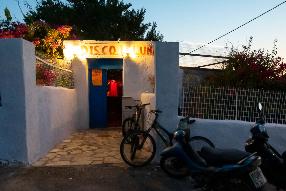 This image shows the quaint entrance to La Luna Disco at sunrise. The entrance is typical of the Greek Islands: Whitewashed wall, blue door and a fuchsia bougainvillea hanging above. There are motorbikes and bicycles parked outside.