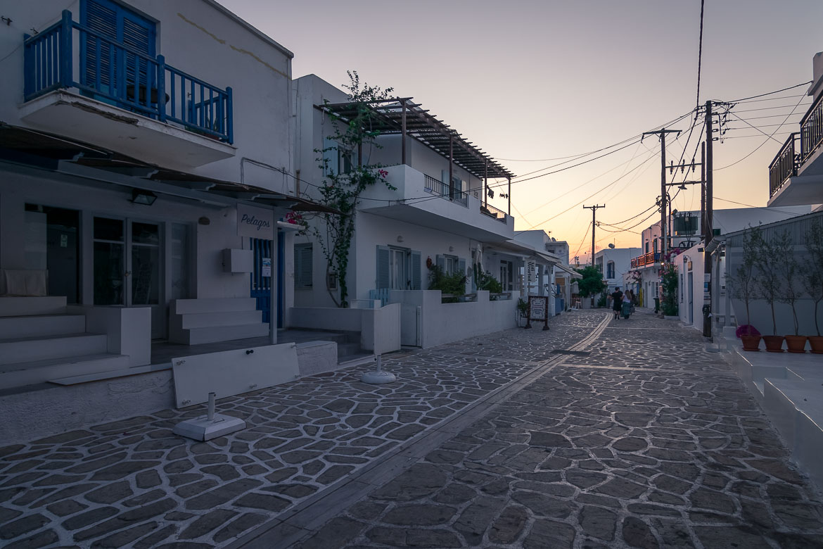 This is an image of the main street in Antiparos Town at sunrise. All shops are closed and there is absolute peace and quiet but for a couple of people who walk around after a night out. In the backgound, the sky is painted orange.