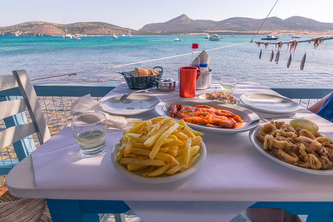 This photo shows a table set for lunch next to the sea at Captain Pipinos traditional tavern. There are french fries, fried calamari, shrimps and wine on the table. In the background, we can see Despotiko Island.