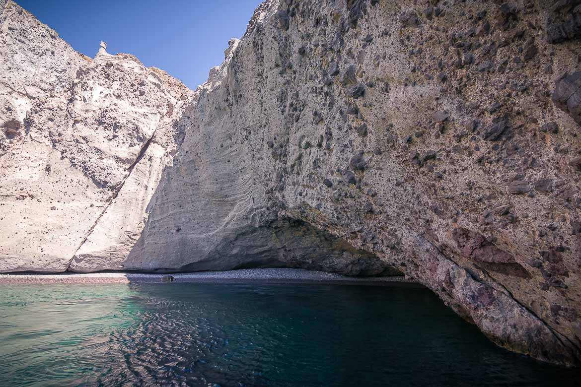 This is a photo of one of the sea caves we visited on a boat tour. The rock and the sand are bright weight and the water is emerald green.