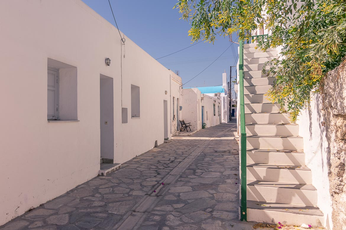 This photo shows a sun kissed narrow pedestrianised street in Antiparos Town.