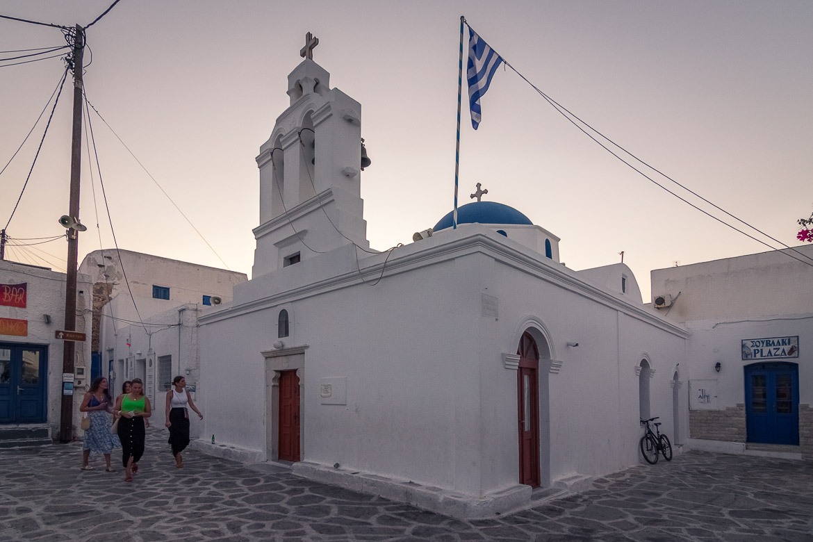 This image shows St Nicholas Church in Chora Antiparos at sunrise. The sky is a beautiful lilac and there are four girls walking past the church. They obviously just came back from a summer night out.