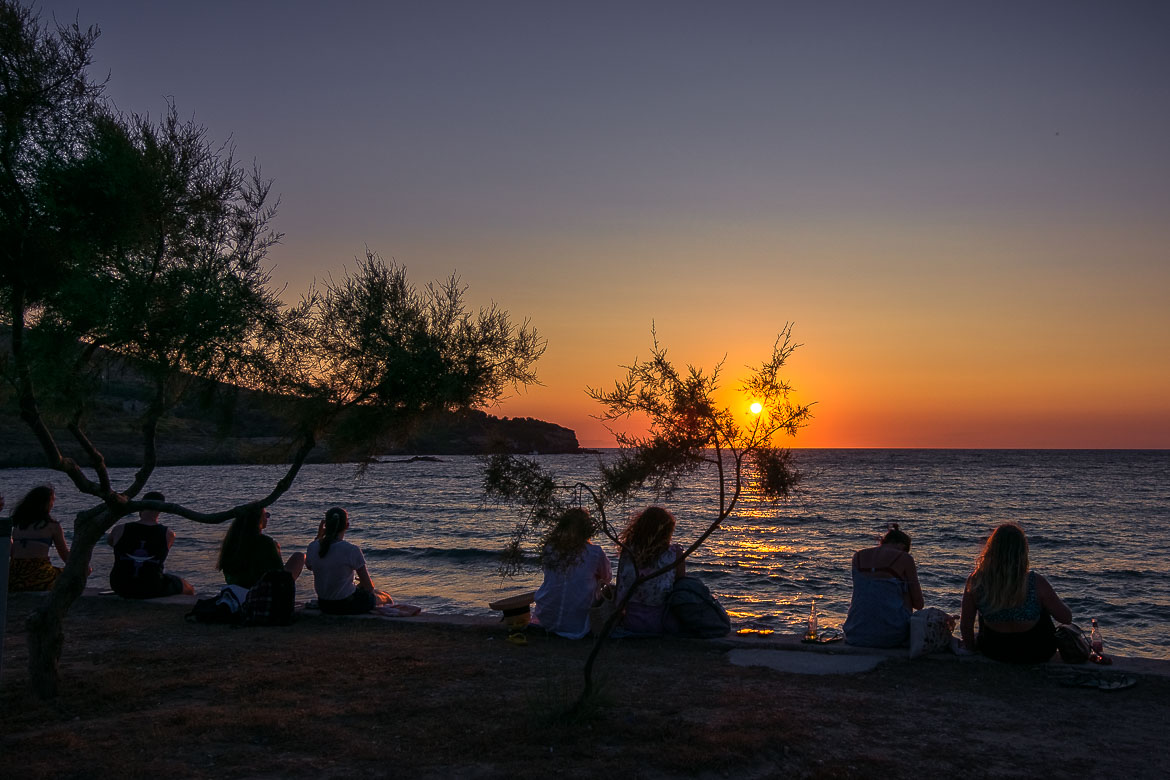This image shows people with their backs turned to the camera watching the sun dive into the sea in the horizon. Watching the sunset at Sifneiko Beach is one of the best things to do in Antiparos Greece.