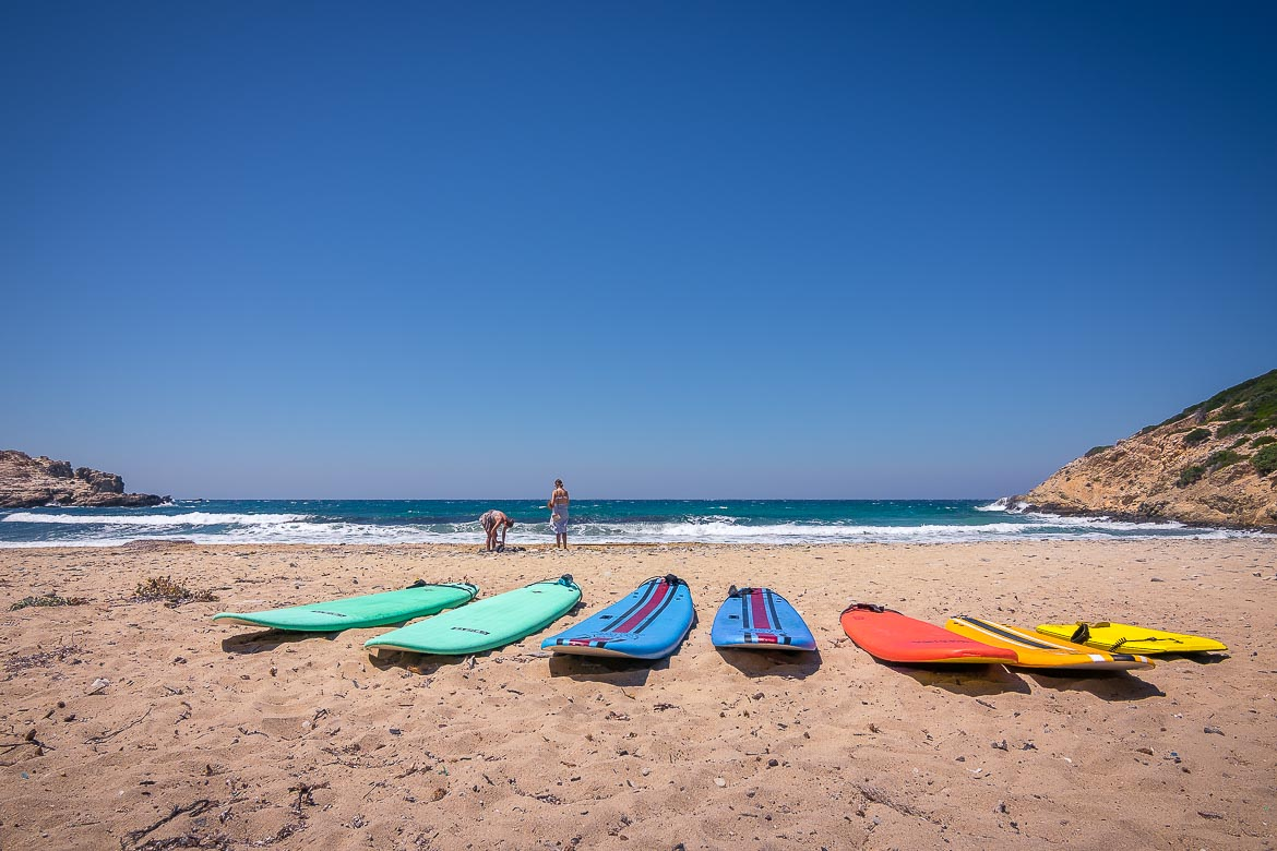 This image shows Livadia, a windy beach in Antiparos. There are huge waves in the sea. In the foreground, there are 7 surfboards of various colours on the golden sand.