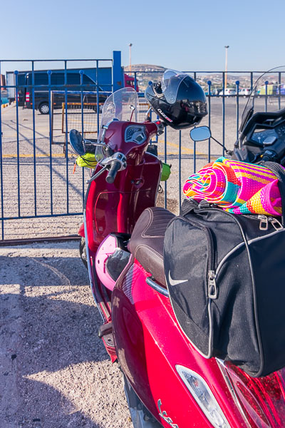 This is a close up of our red vespa loaded with our luggage at the port of Paros.