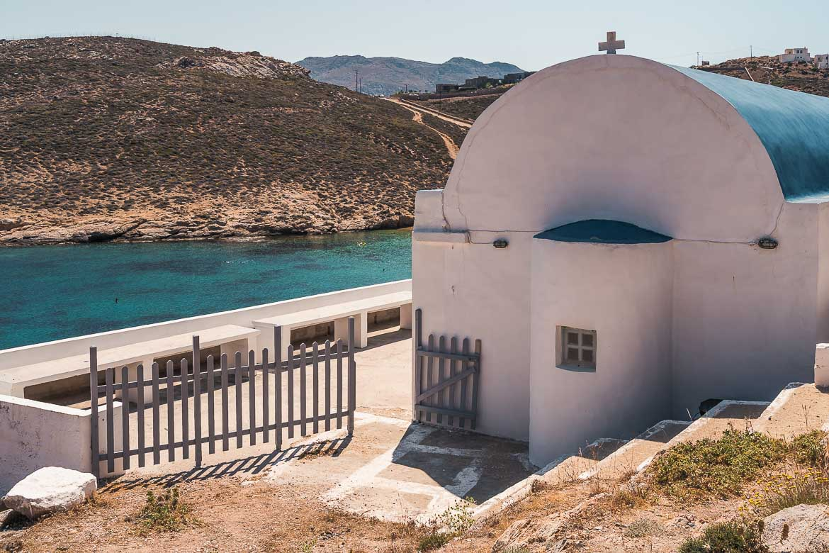 This is a close-up of Agios Sostis Church. In the background, the emerald waters of Agios Sostis Beach.