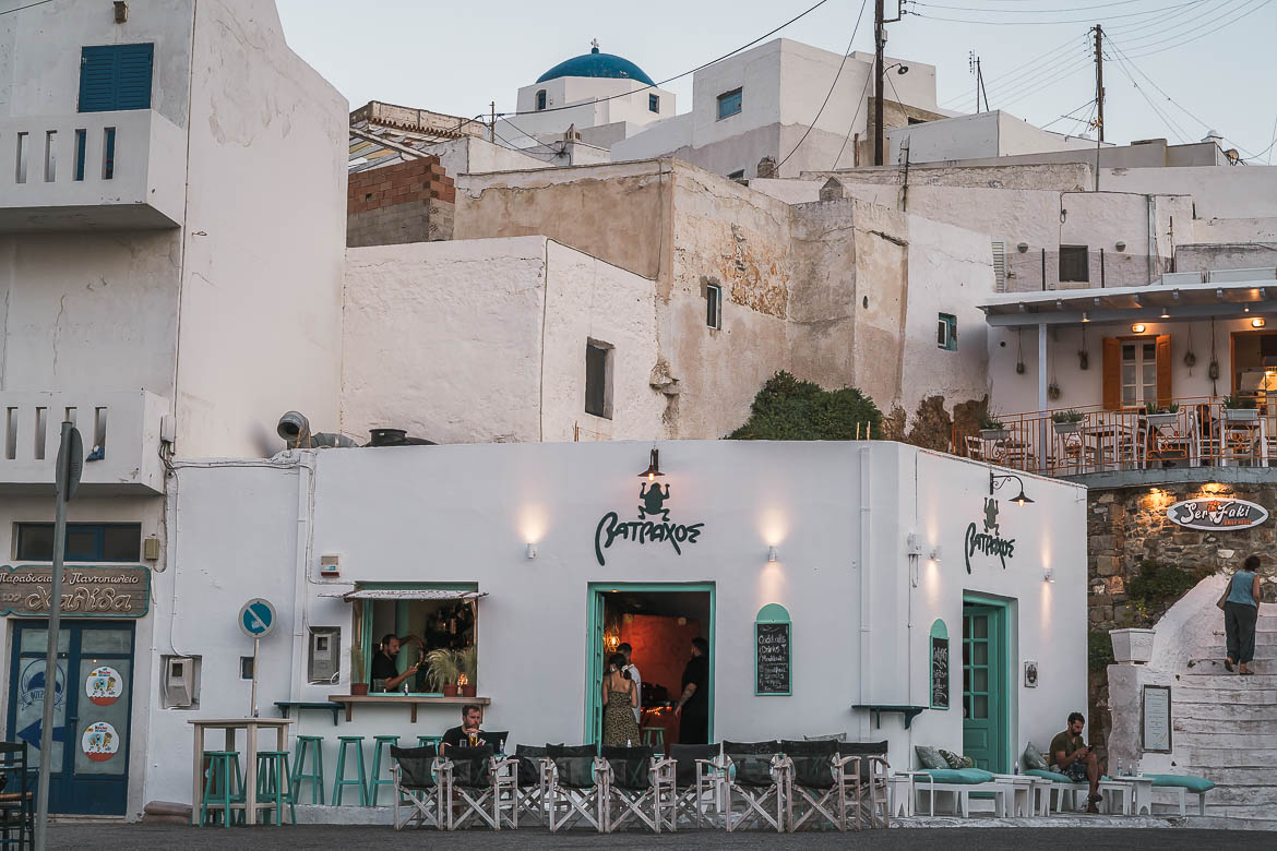 This is an image of Batraxos Bar at dusk. It's a whitewashed building with light green shutters and a sign with a frog.