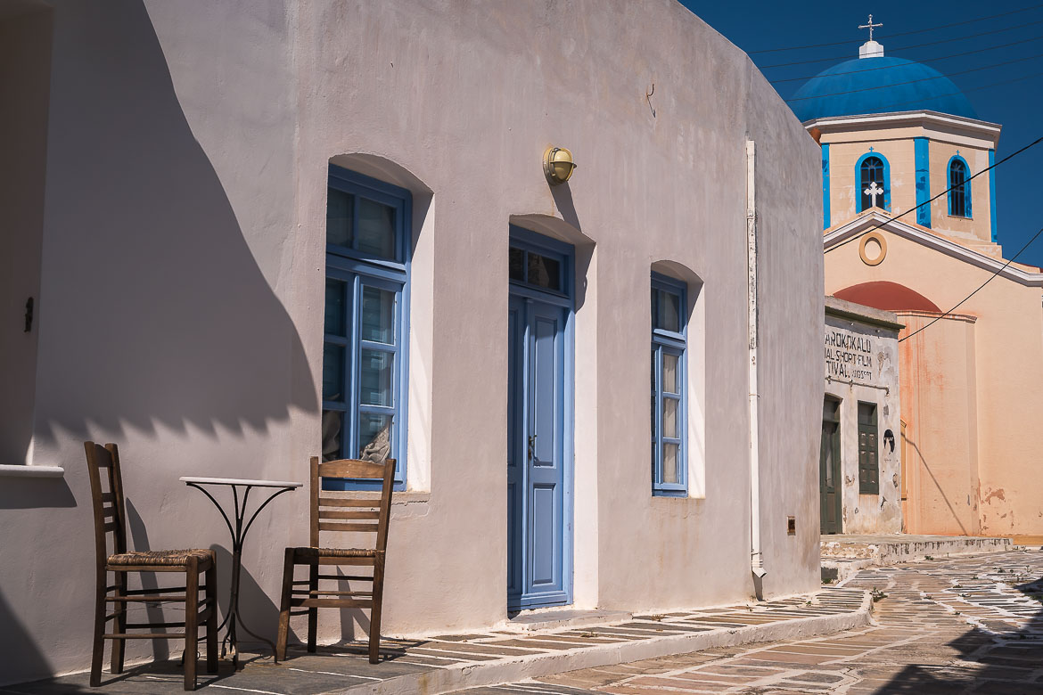 This photo shows a table and two chairs outside a whitewashed house with sky blue doors and shutters in Kato Chora Serifos.
