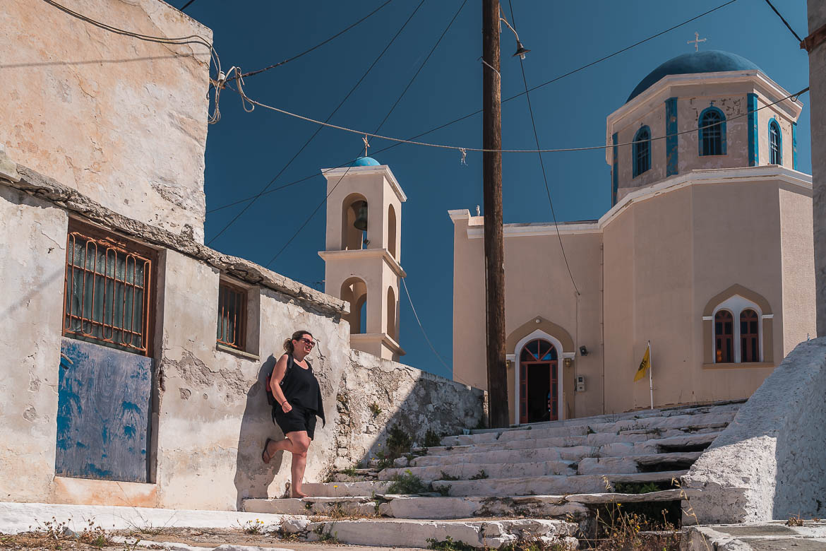 This photo shows Maria leaning on an old wall at Kato Chora. The Church of Evangelistria is in the background.