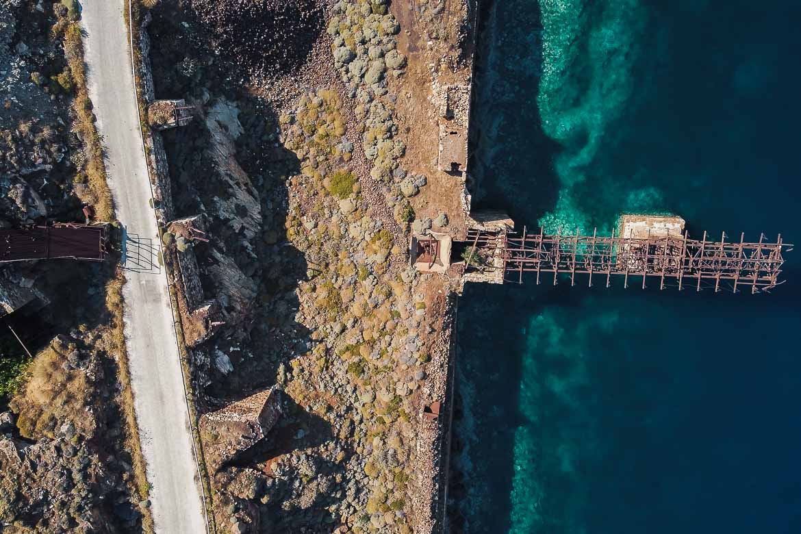 This is a drone shot of the old loading ladder in Koutalas, over the emerald sea.