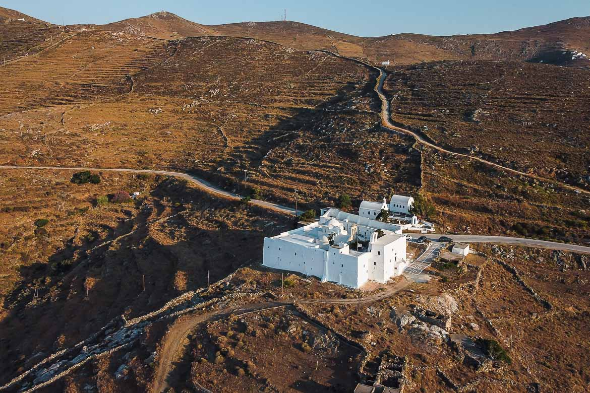 This image shows the monastery of Taxiarches shot from a drone. It looks like a dazzlingly white fortress surrounded by spectacular barren scenery.